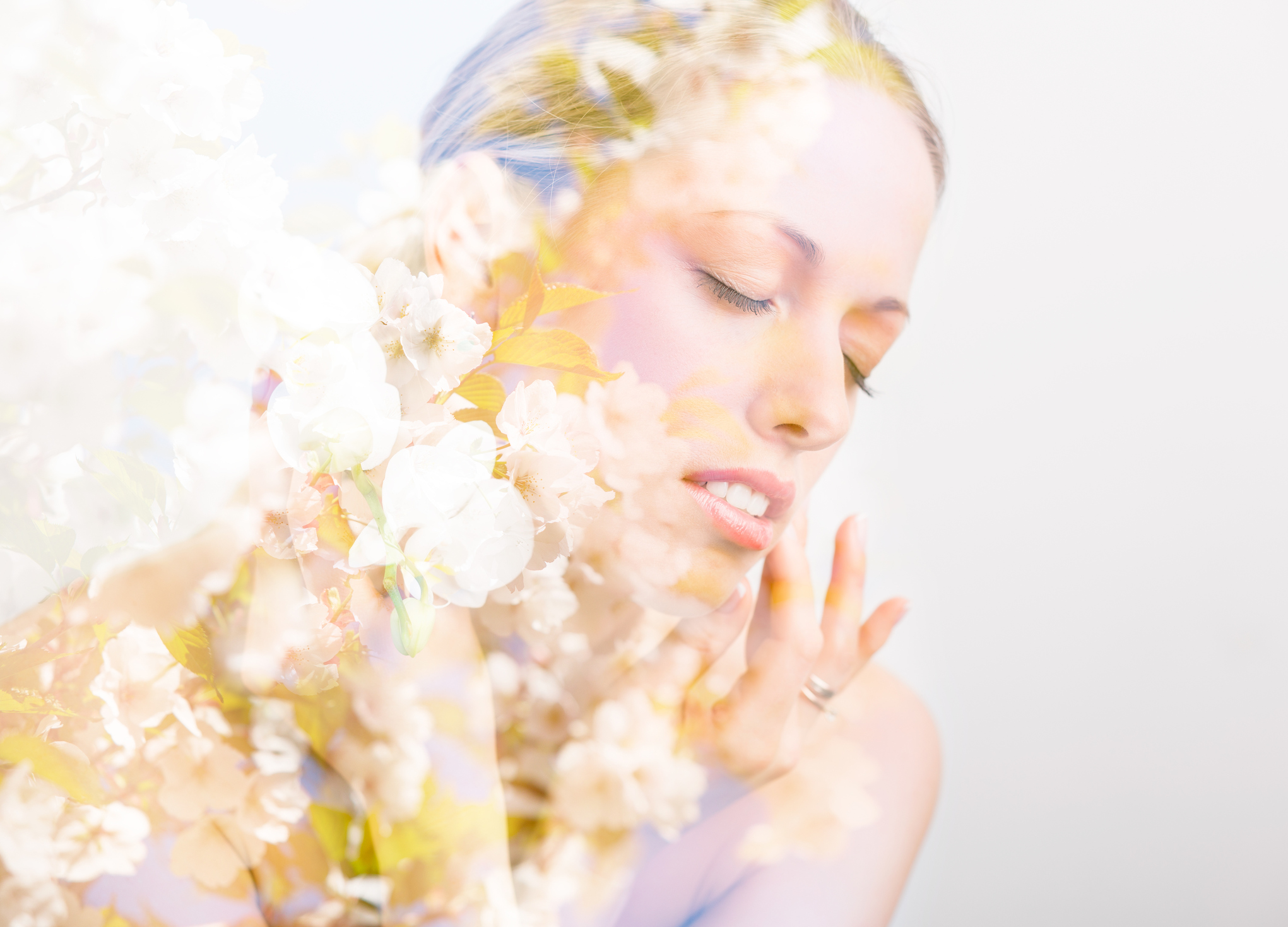 Double exposure photo of beautiful woman's face and flowers